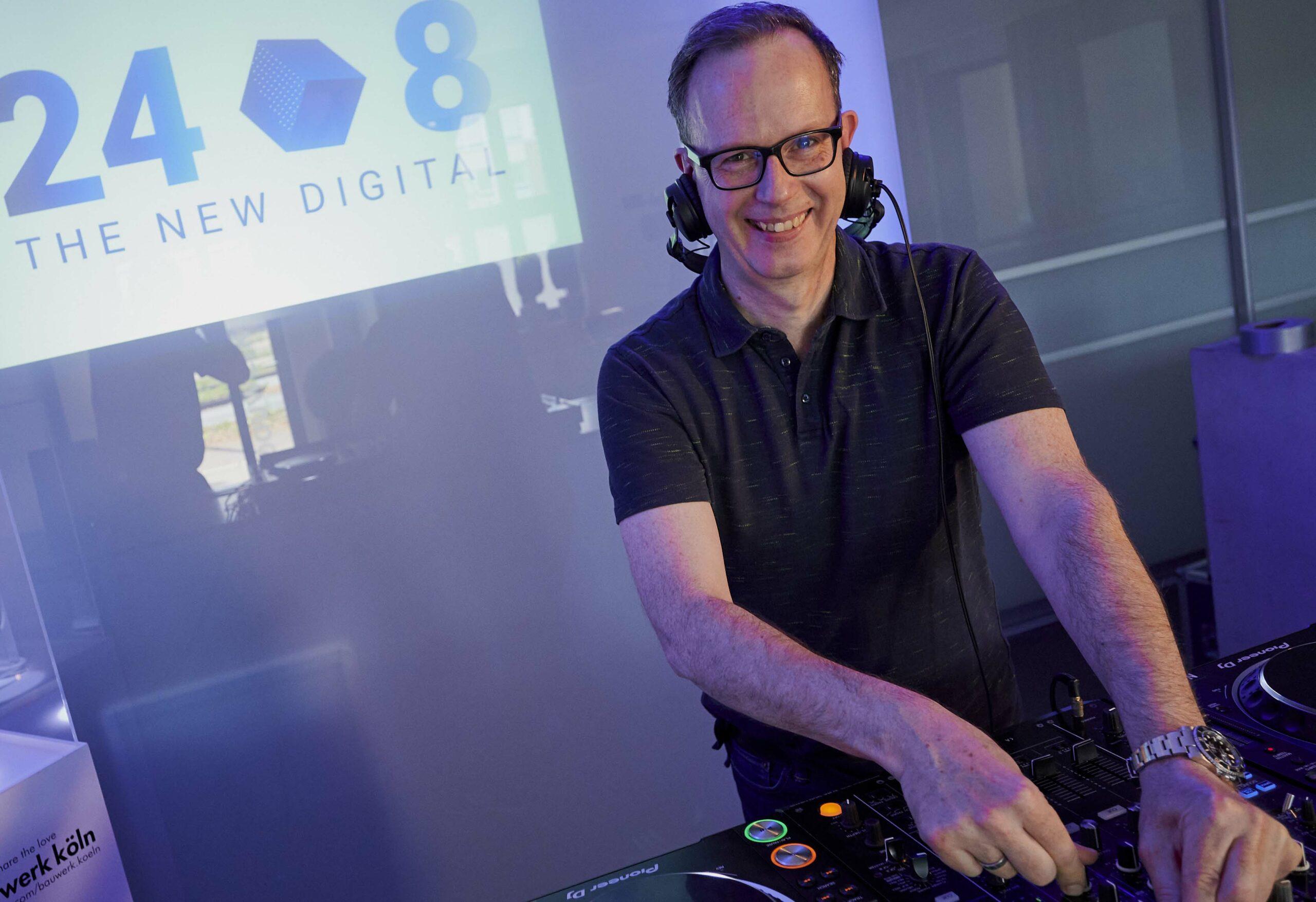 DJ René Pera blickt bei einem Online Event in die Kamera. Im Hintergrund sieht man das Logo 24/8 The New Digital
