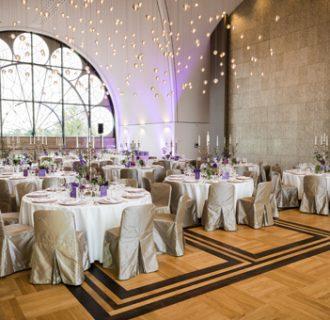 Hochzeits DJ René Pera im Dachsalon der Flora/Köln. Man sieht die festlich gedeckten Tisch und die Stühle mit champagnerfarbigen Hussen. Die Wände haben einen Hauch von Lila als Farbton. Der Raum erstrahlt im Tageslicht.