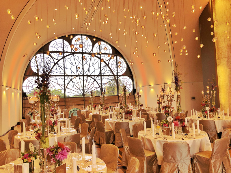 Professioneller DJ René Pera bei einer exklusiven Hochzeitsfeier im Dachsalon/Flora/Köln. Der Raum ist amber gold gefärbt. Die Tische sind festlich gedeckt. Von der Decke hängen Plexiglaskugeln herunter.