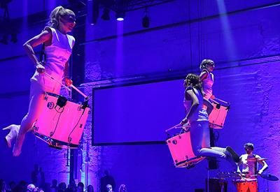 DJ René Pera und drei Percussionisten die an Seilen aufgehängt frei im Raum schweben. Ein vierter Percussionist steht im Hintergrund auf dem Boden.
