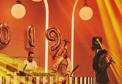 DJ René Pera plus zwei Sängerinnen plus Saxophonistin im Festsaal in der Flora/Köln. Blick fontal auf die Bühne. Die Musikerinnen befinden sich vor dem DJ-Pult.