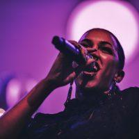DJ René Pera mit der Sängerin Naomi Khimji Feld. Auf dem Bild ist Naomi vor lila farbenem Hintergrund zu sehen.