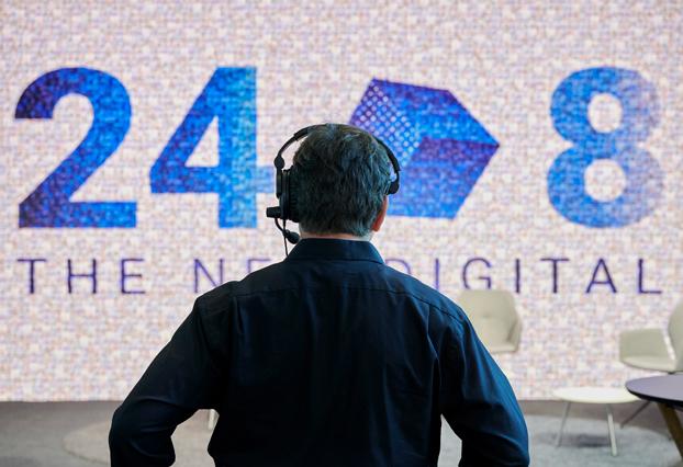 Regisseur steht mit dem Rücken zur Kamera vor einer Leinwand bei einem Online-Event mit DJ René Pera.
